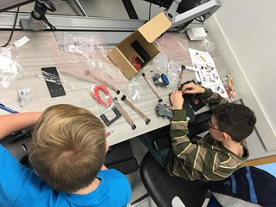 Scout building robot with parts laid out